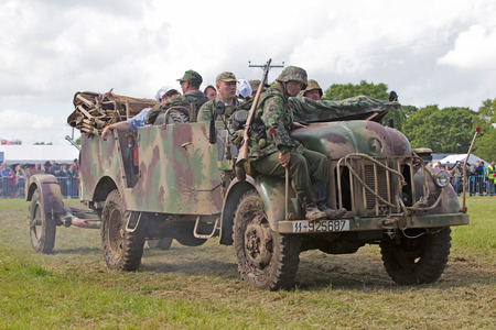 wehrmacht: DENMEAD, UK - MAY 25: WW2 German army reenactors prepare to position their truck and field gun into place for the upcoming battle re-enactment at the Overlord show on May 25, 2014 in Denmead