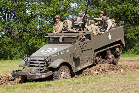 reenactor: DENMEAD, UK - MAY 25: US army reenactors from the WW2 period take their halftrack into a tank ditch during a battle re-enactment for the public to watch at the Overlord show on May 25, 2014 in Denmead