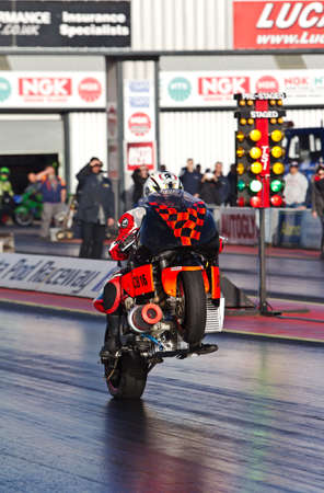 dragster: PODINGTON, UK - OCTOBER 19: An unnamed rider takes his dragster motorcycle down the Santa Pod raceway at speed during the Extreme Performance Bike event on October 19, 2014 in Podington