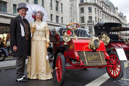 vestidos de epoca: LONDRES - 01 de noviembre: Un coche del veterano y los propietarios vestidos con trajes de �poca aut�ntica l�nea de arriba en el centro de la carretera para una exhibici�n est�tica en la feria anual de motor calle Regent en 01 de noviembre 2014