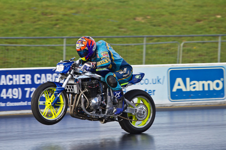 unnamed: PODINGTON, UK - OCTOBER 19: An unnamed rider takes his drag street bike motorcycle down the Santa Pod raceway at speed during the Extreme Performance Bike event on October 19, 2014 in Podington Editorial