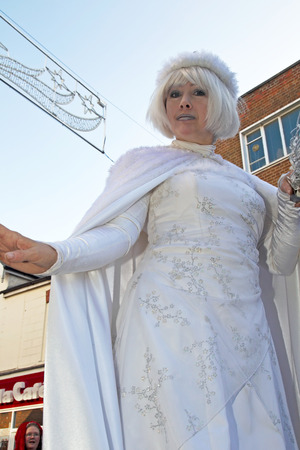 parades: AYLESBURY, UK - NOVEMBER 30: A female performer dressed as the White Queen parades through Aylesbury with other festival acts as part of the Christmas festivities on November 30, 2014 in Aylesbury Editorial