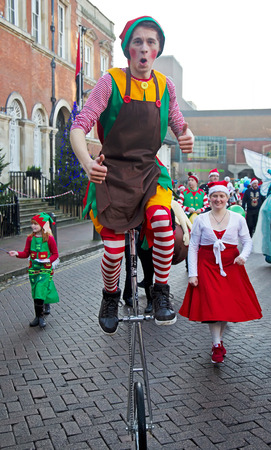 fayre: AYLESBURY, UK - NOVEMBER 30: A unicyclist performer parades through the market square in Aylesbury along with other carnival acts as part of the Christmas festivities on November 30, 2014 in Aylesbury Editorial