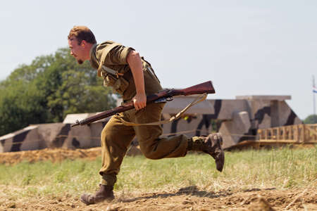 infantryman: WESTERNHANGER, UK - JULY 18: A British army WW2 reenactor runs for cover while advancing on enemy positions during a WW2 battle reenactment scene at the WP show on July 18, 2014 in Westernhanger