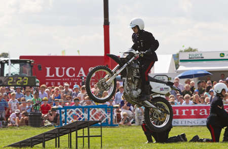 showground: WEEDON, UK - AUGUST 29: Members of the Royal Signals White Helmets display team demonstrate a jump stunt for the public at the Bucks County show on August 29, 2013 in Weedon