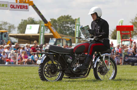 specialised: WEEDON, UK - AUGUST 29: A rider of the Royal Signals White Helmets display team demonstrates riding a motorcycle backwards for the public at the Bucks County show on August 29, 2013 in Weedon