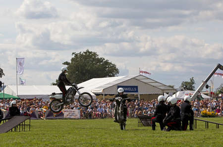 the royal county: WEEDON, UK - AUGUST 29: Members of the Royal Signals White Helmets display team demonstrate a synchronised jump stunt for the public at the Bucks County show on August 29, 2013 in Weedon