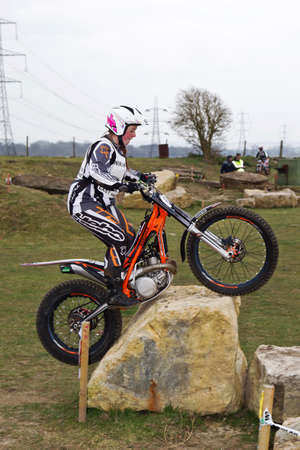 trials: CHOLSEY, UK - MARCH 15: Jess Bown competing in Rd1 of the Ladies UK national trials championship rides over a large rock boulder to start the section at Seymours arena on March 15, 2015 in Cholsey
