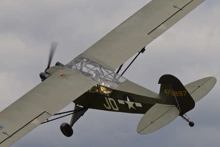 recon: HEADCORN, UK - AUGUST 16: A WW2 US army Piper Cub recon aircraft does a low level flypast as part of a re-enactment scene at the Combined-Ops military show on August 16, 2014 at Headcorn Editorial