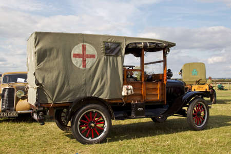 ww1: HEADCORN, UK - AUGUST 16: A WW1 period Model T ambulance leaves its stabling point en route to the main arena to give a public display at the Combined-Ops military show on August 16, 2014 at Headcorn