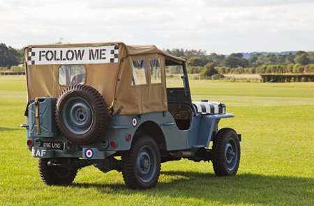 raf: HEADCORN, UK - AUGUST 16: A vintage WW2 RAF Jeep stands at readiness to help with aircraft landing on the grass runway if needed at the Combined-Ops military show on August 16, 2014 at Headcorn