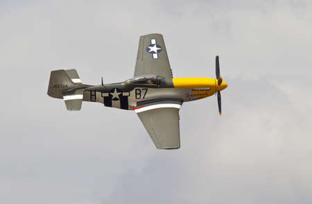 ww2: LONDON- JUNE 14: A vintage P51 Mustang fighter aircraft from the WW2 era gives an aerial display to the watching public during a north London air show on June 14, 2014 in London Editorial