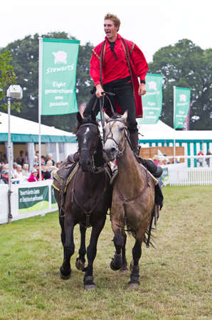hants: BROCKENHURST, UK - JULY 31: Riders of the Devils Horsemen display race around the show ring standing on the back of two horses at the New Forest  Hants County Show on July 31, 2013 in Brockenhurst