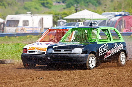 unnamed: STROUD, UK - MAY 3: Unnamed drivers competing in Rd1 of the 2014 UKAC autograss series come together at the top corner of the circuit as they complete lap 3 of the heat on May 3, 2014 in Stroud