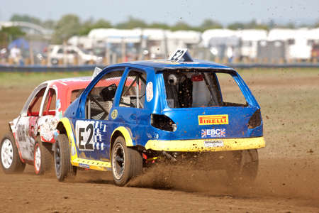 unnamed: STROUD, UK - MAY 3: Unnamed drivers competing in Rd1 of the 2014 UKAC autograss series come together at the exit of a corner in their class 4 vehicles during a heats race on May 3, 2014 in Stroud Editorial