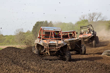 berm: ARNCOTT, UK - MAY 4: Unnamed drivers competing in the UK SXS RZR series round a tight berm and corner at speed before heading toward the finish line on May 4, 2014 in Arncott Editorial