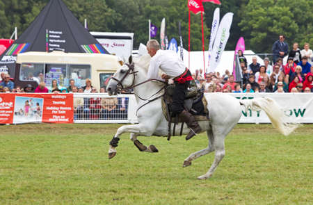 hants: BROCKENHURST, UK - JULY 31: Riders of the Devils Horsemen display team race around the show ring performing high speed stunts at the New Forest  Hants County Show on July 31, 2013 in Brockenhurst Editorial