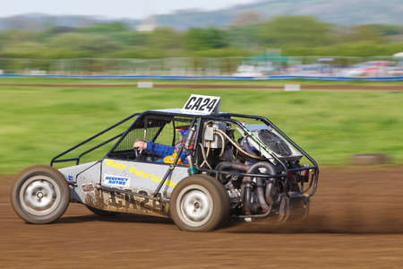 exits: STROUD, UK - MAY 3: An unnamed driver competing in Rd1 of the 2014 UKAC autograss series exits the top corner of the circuit at speed in a class10 vehicle during a heat race on May 3, 2014 in Stroud