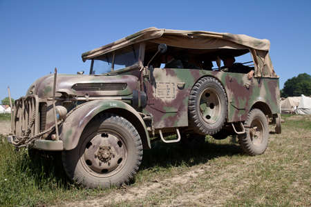troop: WESTERNHANGER, UK - JULY 19: A WW2 German army troop truck is parked at the edge of the battle field during a battle re-enactment at the War  Peace show on July 19, 2013 in Westernhanger