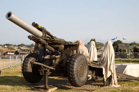artillery shell: WESTERNHANGER, UK - JULY 18: A vintage WW2 allied howitzer artillery gun is covered up overnight before going on public display at the War  Peace show on July 18, 2013 in Westernhanger