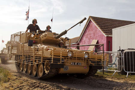 anti war: WESTERNHANGER, UK - JULY 17: An ex British army Sabre tank with anti IED caging leaves the main arena having given a display to the public at the War  Peace show on July 17, 2013 in Westernhanger Editorial
