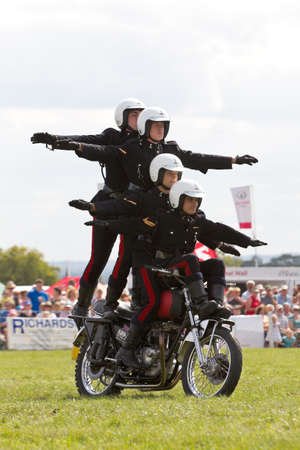 showground: WEEDON, UK - AUGUST 29: Riders of the Royal Signals White Helmets display team demonstrate formation riding on a single motorcycle for the public at the Bucks County show on August 29, 2013 in Weedon Editorial