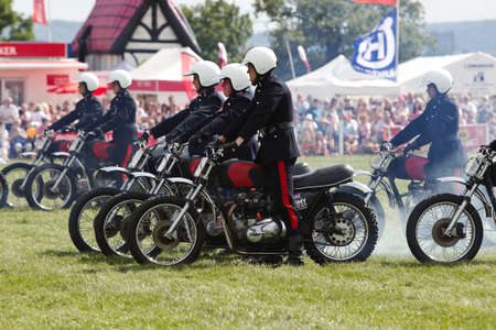 showground: WEEDON, UK - AUGUST 29: Riders of the Royal Signals White Helmets display team demonstrate formation riding on motorcycles for the public at the Bucks County show on August 29, 2013 in Weedon Editorial