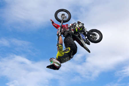 showground: WEEDON, UK - AUGUST 27: A rider performing freestyle FMX stunts completes a full 360 degree loop on a minibike for the watching public at the Bucks County show on August 27, 2015 in Weedon Editorial