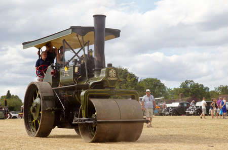 steam traction: POTTEN END, UK - JULY 27: A large vintage traction engine leaves the show grounds heading toward the departure and loading area at the Dacorum Steam fair on July 27, 2014 in Potten End