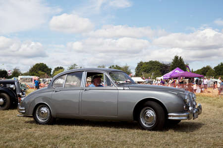 sportscar: POTTEN END, UK - JULY 27: A vintage Jaguar MkII luxury sportscar exits the show arena having just given a public display at the Dacorum Steam Fair on July 27, 2014 in Potten End. Editorial