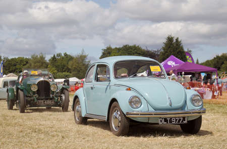 motorcar: POTTEN END, UK - JULY 27: A classic Volkswagen Beetle motorcar leaves the main display arena having just completed its show to the public at the Dacorum Steam fair on July 27, 2014 in Potten End