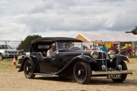 earlier: POTTEN END, UK - JULY 27: A vintage 1934 Jaguar SS1 luxury tourer car exits the show grounds having given a public display earlier in the day at the Dacorum Steam Fair on July 27, 2014 in Potten End. Editorial