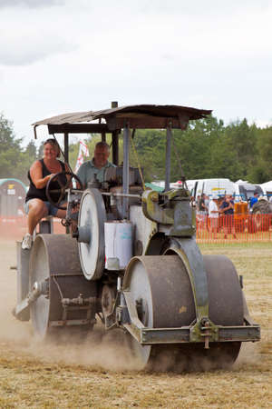 steam roller: POTTEN END, UK - JULY 27: A large vintage road roller gives a display to the public around the main display arena at the Dacorum Steam fair on July 27, 2014 in Potten End
