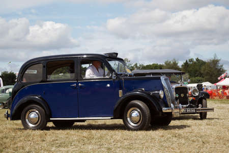 motorcar: POTTEN END, UK - JULY 27: A vintage London taxi cab exits the show arena having just given a public display at the Dacorum Steam Fair on July 27, 2014 in Potten End. Editorial