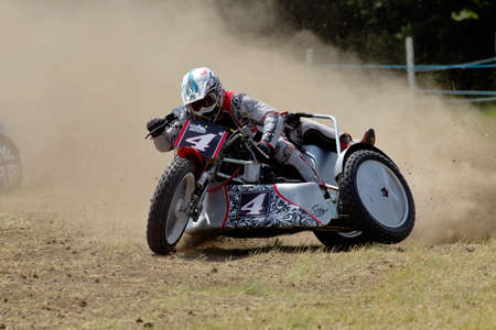 unnamed: PUTTENHAM, UK - JULY 14: An unnamed sidecar team speed around the top corner of the circuit in first place during the Puttenham grasstrack meeting on July 14, 2013 in Puttenham.
