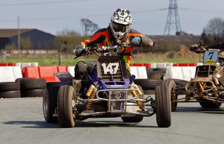 unnamed: OSWESTRY, UK - APRIL 27: An unnamed rider competing in the NoraSport UK quad bike championship negotiates a tight corner exit at the Rednal race circuit on April 27, 2013 in Oswestry