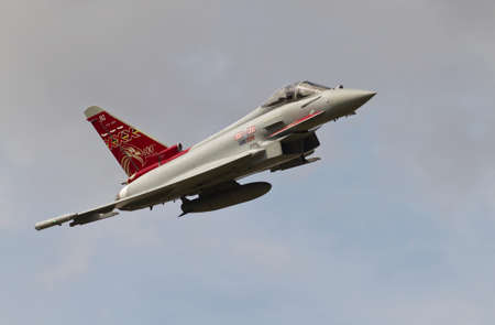 aerodrome: STANDEN, UK - AUGUST 15: An RAF Typhoon fighter jet exits the area having flown the flight line along Headcorn aerodrome during the Combined Ops military show on August 15, 2015 in Standen