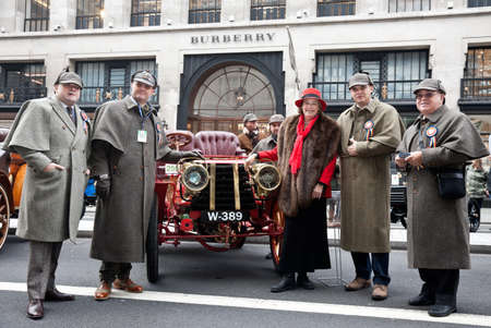 london to brighton veteran car run: LONDON - OCTOBER 31: Participants in the annual London to Brighton veteran car run pose in front of their car dressed in period garb at the Regent Street classic car show on October 31, 2015 in London