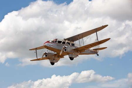aerodrome: NORTHILL, UK - JULY 5: A vintage DeHavilland Rapide biplane gives short trips for paying customers during one of the air displays hosted at the Old Warden aerodrome on July 5, 2015 in Northill