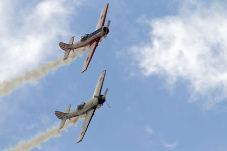 monoplane: NORTHILL, UK - JULY 5: A pair of vintage Russian built Yak aircraft give an aerial aerobatics display to the crowd below inside Old Warden aerodrome on July 5, 2015 in Northill