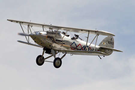 aerodrome: KINGSHILL, UK - AUGUST 2: A vintage demobbed RAF Hawker Demon biplane completes a circuit of the Old Warden aerodrome before coming into land on August 2, 2015 in Kingshill Editorial