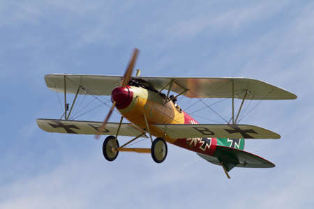 ww1: NORTHILL, UK - AUGUST 2: A replica Albatross Dv fighter aircraft from the WW1 Luftwaffe era prepares to land on the grass runway at Old Warden aerodrome on August 2, 2015 in Northill Editorial