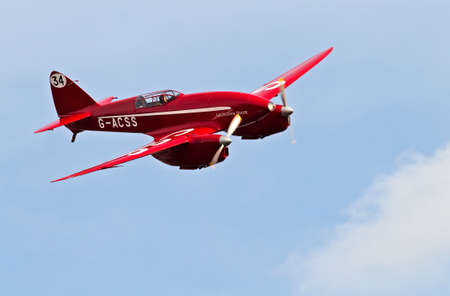 aerodrome: NORTHILL, UK - OCTOBER 5: A DH88 Comet racing aircraft manoeuvres into position for landing at the Old Warden aerodrome on October 5, 2014 in Northill. The DH88 was first built in 1934 for £5K  unit Editorial