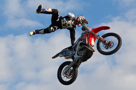manoeuvre: NEWBURY, UK - SEPTEMBER 21: An FMX stunt rider completes a mid air off the bike manoeuvre for the watching crowd at the Berks County show on September 21, 2014 in Newbury Editorial