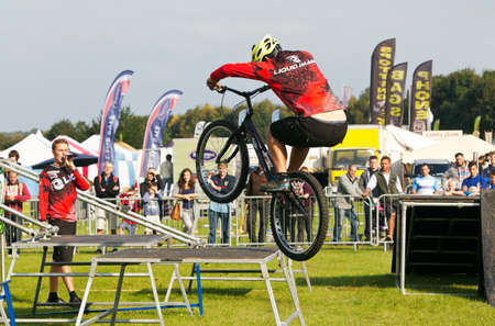 prowess: NEWBURY, UK - SEPTEMBER 21: A rider from a freestyle BMX team displays his stunting prowess to the watching public as part of the entertainment show at the Berks show on September 21, 2014 in Newbury