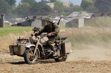 sidecar: WESTERNHANGER, UK - JULY 20: A motorcycle and sidecar team head around a dusty main arena during a public performance at the War & Peace Revival show on July 20, 2016 in Westernhanger