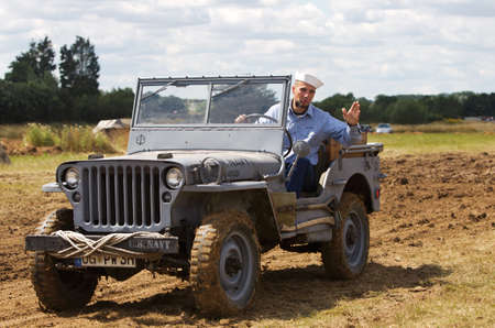 reenactor: WESTERNHANGER, UK - JULY 25: A WW2 period USN reenactor and jeep parade around the main show arena for the public to watch at the War & Peace show on July 25, 2015 in Westernhanger