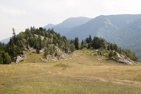 Mountainous landscape with a forested rocky outcrop rising above open fields with dirt tracks or trails for hiking Standard-Bild