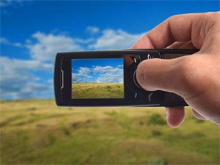 Shooting landscape with mobile phone. Photo on screen and background is my own shot.  Stock Photo
