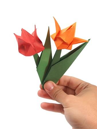 Origami tulip on hand over white  photo